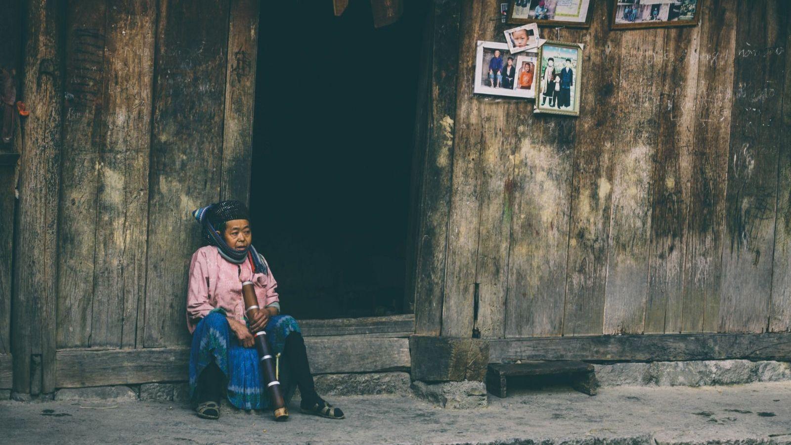 cụ già ngồi hút thuốc lào trước bậc cửa của căn nhà cổ