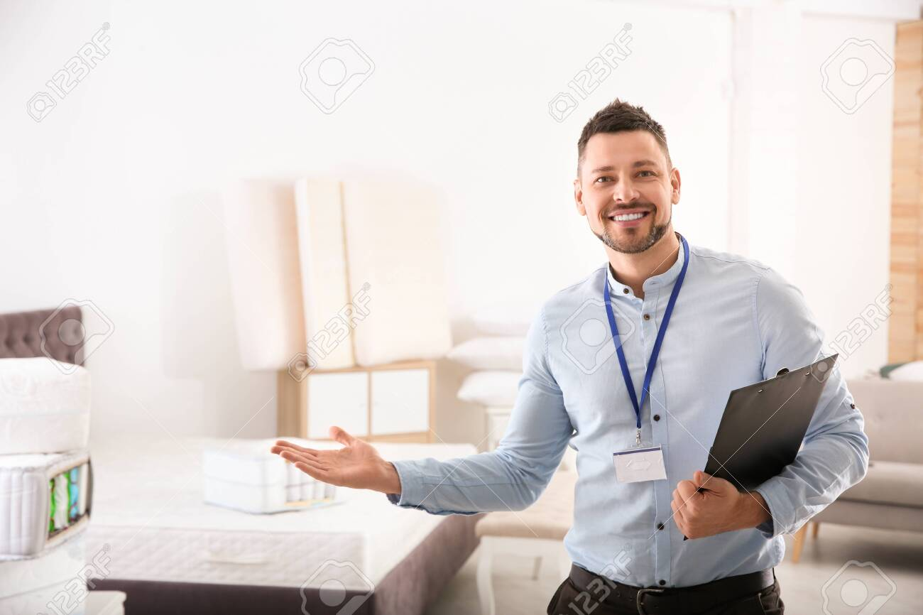 Happy Salesman With Clipboard In Mattress Store. Space For Text Stock  Photo, Picture And Royalty Free Image. Image 140357062.
